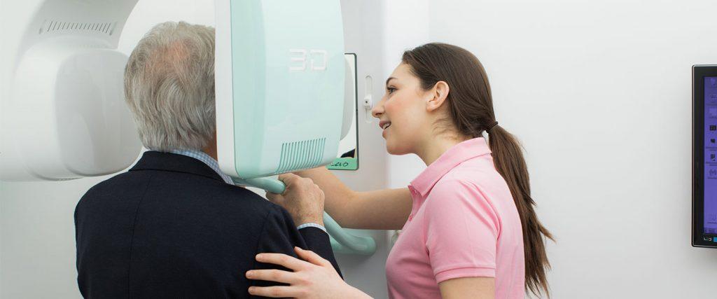Assistentin betreut älteren Patienten bei der digitalen Volumentomographie in der Zahnarztpraxis in Wien