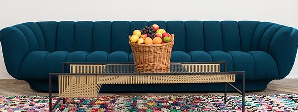 Einladende Couch mit frischen Früchten im Wartebereich der Zahnarztpraxis Dr. Andreas Quidenus in Wien