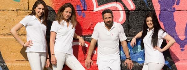 Das Team um Zahnarzt Dr. Andreas Quidenus vor künstlerischer Wand in Wien