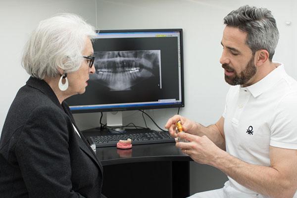 Zahnarzt Dr. Andreas Quidenus zeigt seiner Patientin das Modell eines Zahnimplantates.