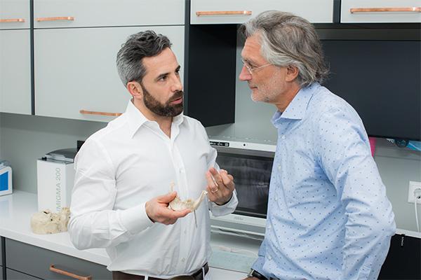 Zahnarzt Dr. Andreas Quidenus erklärt älterem Patienten am Gebiss-Modell den optimalen Biss