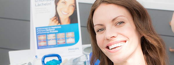 Patientin lacht mit strahlend weißen Zähnen im Bleaching Behandlungszimmer der Zahnarztpraxis Dr. Andreas Quidenus in Wien