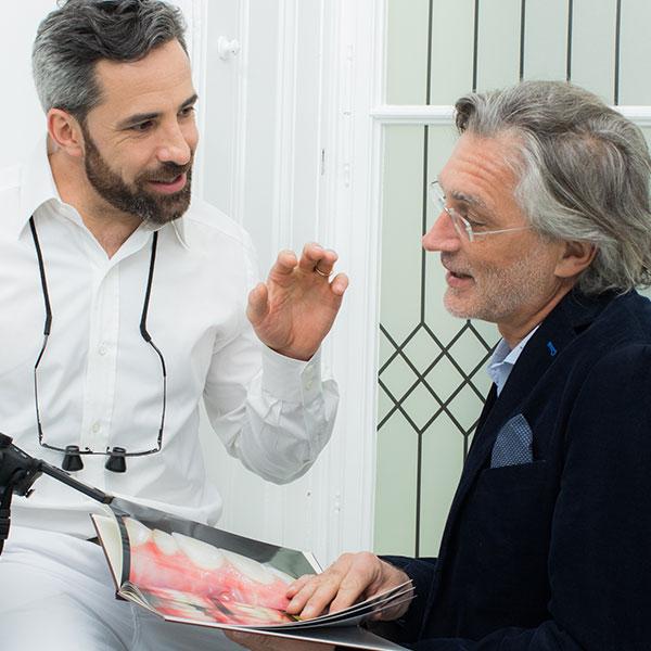 Dr. Andreas Quidenus zeigt älterem Patienten die Ergebnisse einer erfolgreichen Behandlung mit Zahnimplantaten
