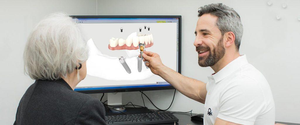 Zahnarzt Dr. Andreas Quidenus und seine ältere Patientin in einer Beratungssituation am All-on-4 Modell