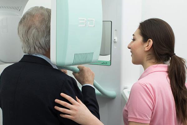 Zahnärztliche Assistentin betreut älteren Patienten bei der digitalen Volumentomographie in der Zahnarztpraxis in Wien