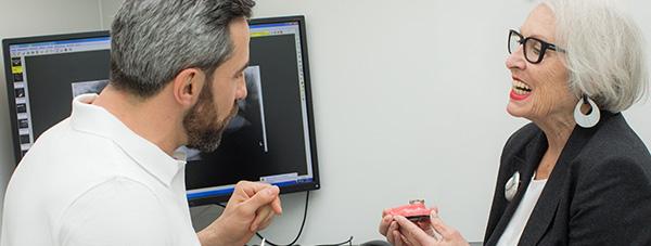 Zahnarzt Dr. Andreas Quidenus erklärt Patientin das Prinzip von Festen Zähnen auf Zahnimplantaten