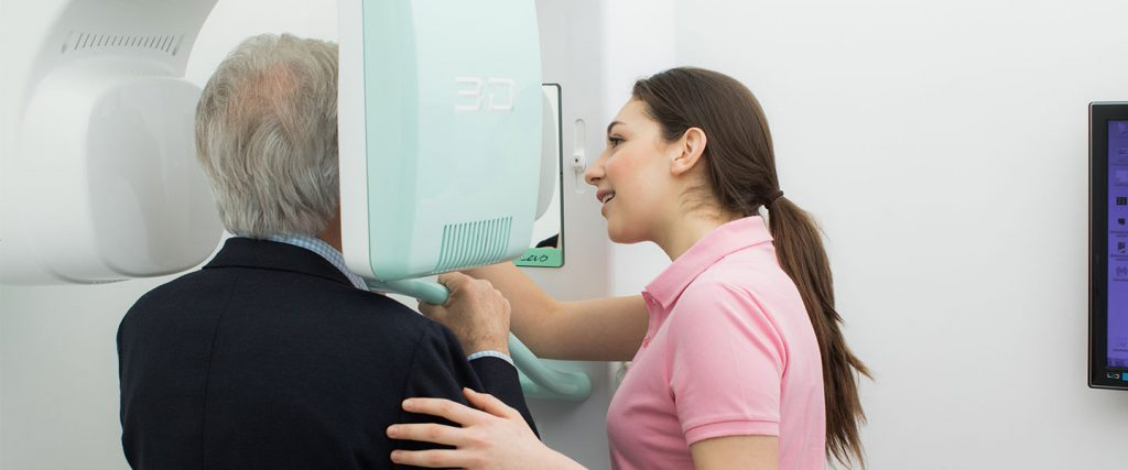 Assistentin betreut älteren Patienten bei der digitalen Volumentomographie in der Implantologie Wien