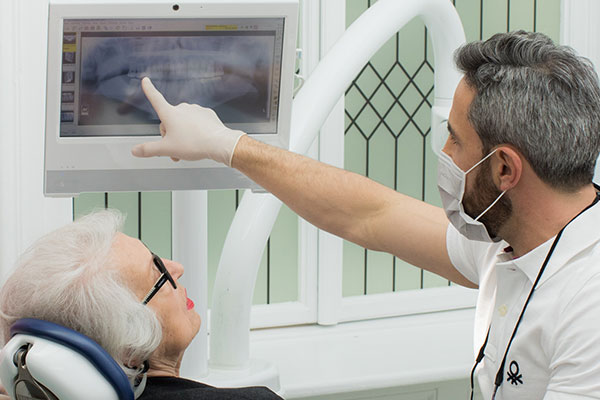 Zahnarzt Dr. Andreas Quidenus erklärt zusammen mit seiner Assistentin einer älteren Patientin die zahnärztliche Chirurgie anhand eines Röntgenbildes
