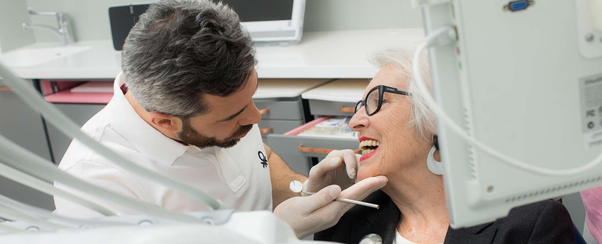 Zahnarzt Dr. Andreas Quidenus untersucht das Gebiss einer älteren Patientin im Behandlungszimmer