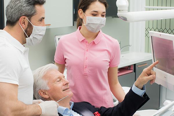 Patient hat Fragen zur Behandlung mit Zahnimplantaten an Dr. Andreas Quidenus und seine Assistentin