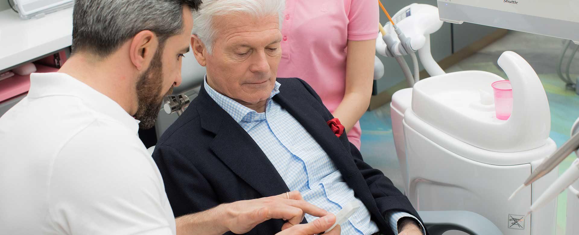 Zahnarzt Dr. Andreas Quidenus erklärt älterem Patienten seine Philosophie für Gesundheit, Fitness und Leistungsfähigkeit
