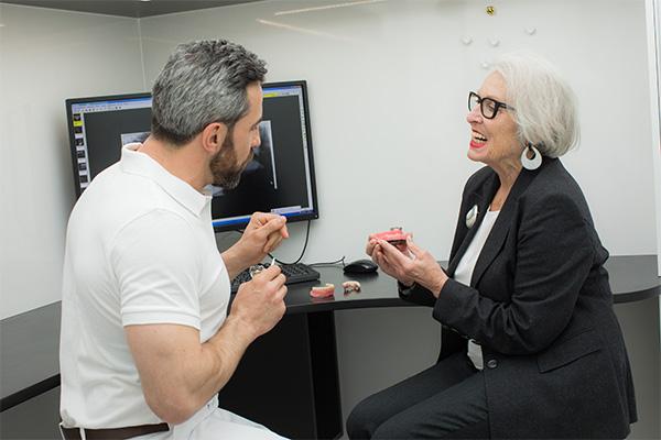 Zahnarzt Dr. Andreas Quidenus erklärt Patientin den Zahnersatz auf Zahnimplantaten
