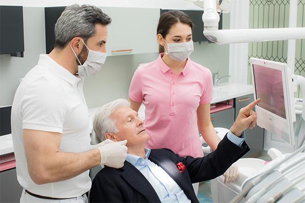 Zahnarzt Dr. Andreas Quidenus in Wien erklärt älterem Patienten zusammen mit seiner Assistenz die Parodontitis-Therapie