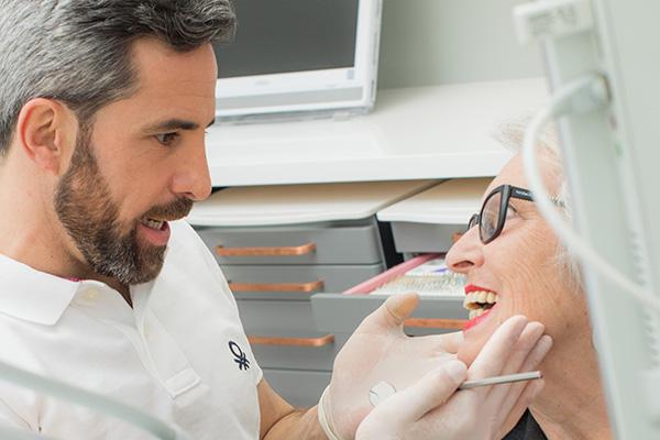 Zahnarzt Dr. Andreas Quidenus betrachtet das Ergebnis des ästhetisch-funktionellen Zahnersatzes bei seiner Patientin