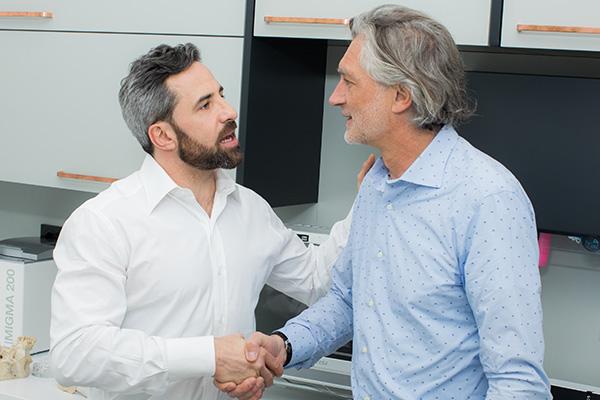 Zahnarzt Dr. Andreas Quidenus begrüßt Patienten zur Behandlung in mit All on 4 Wien