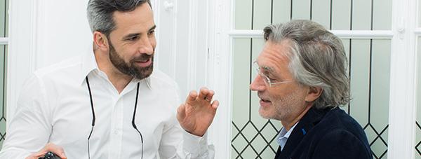Zahnarzt Dr. Andreas Quidenus zeigt älterem Patienten die Ergebnisse einer erfolgreichen Behandlung mit Zahnimplantaten