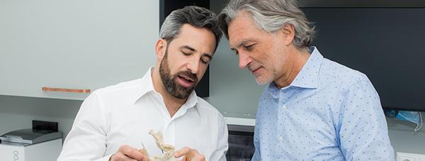 Zahnarzt Dr. Andreas Quidenus erklärt älterem Patienten am Modell eines Unterkiefers den Knochenaufbau