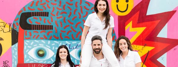 Zahnarzt Dr. Andreas Quidenus hebt Assistentin sportlich auf seinen Schultern und posiert mit dem gesamten Team vor künstlerischer Wand in Wien