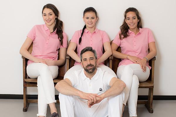 Zahnarzt Dr. Andreas Quidenus sitzt vor seinem Praxisteam