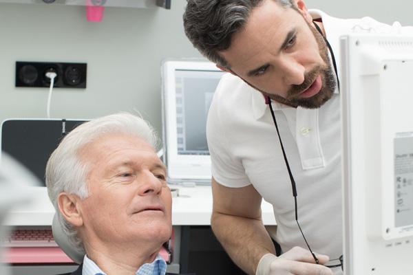 Zahnarzt Dr. Andreas Quidenus bei seiner Erklärung zur Parondotalen Chirurgie mit älterem Patienten vor Monitor