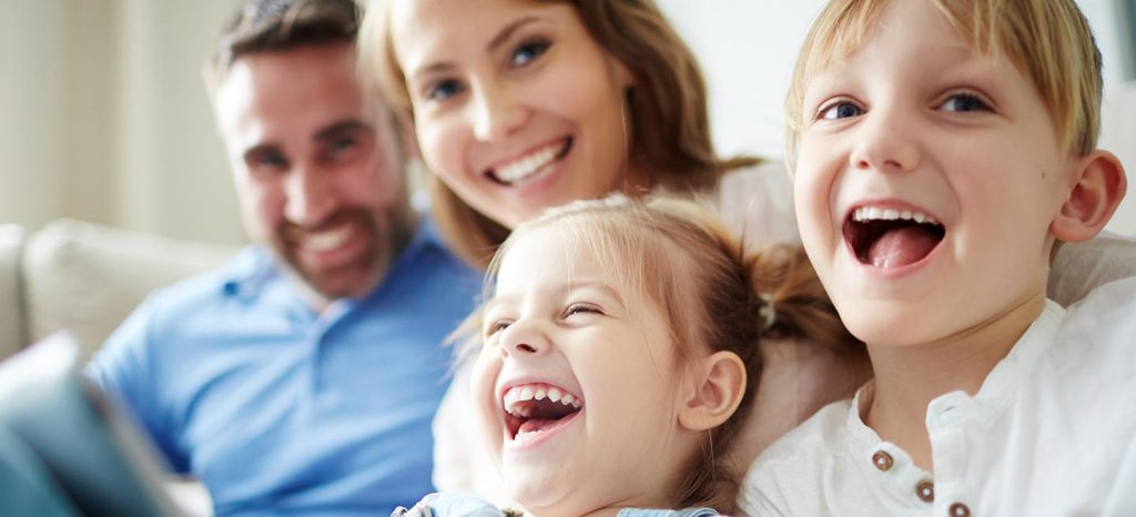 Zwei Kinder lachen zuhause gemeinsam mit Ihren Eltern