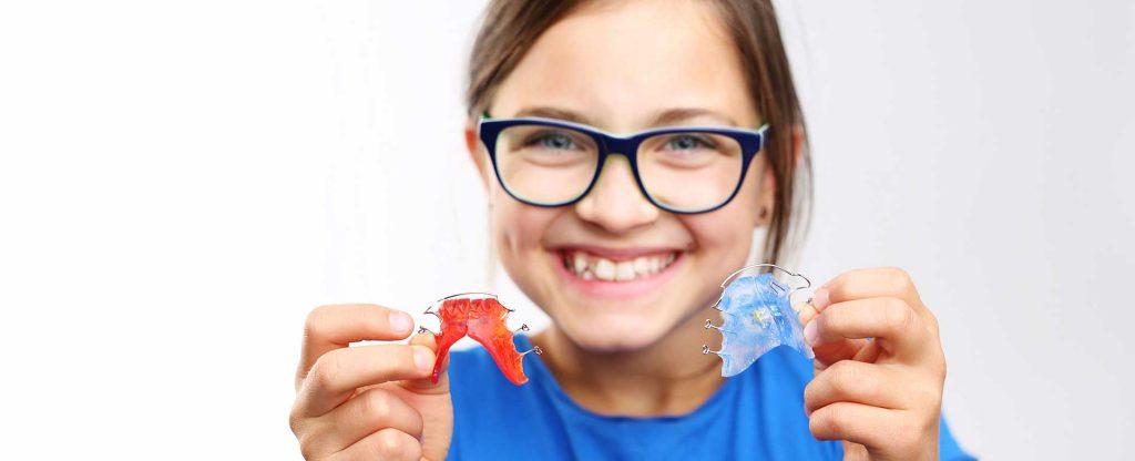 Junges Mädchen präsentiert fröhlich zwei herausnehmbare Zahnspangen bei Ihrem Zahnarzt in Wien
