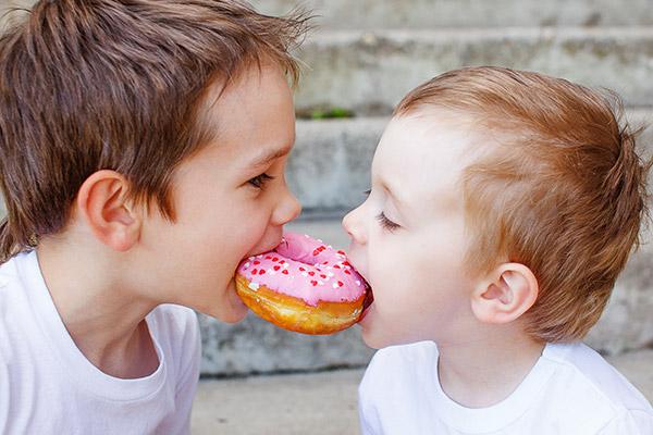 Zwei kleine Jungs beißen gemeinsam in zuckerüberzogenen Donut