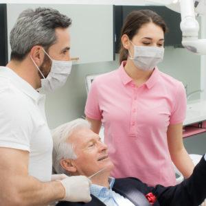 Dr. Quidenus und Team mit Mundschutz bei der Behandlung.