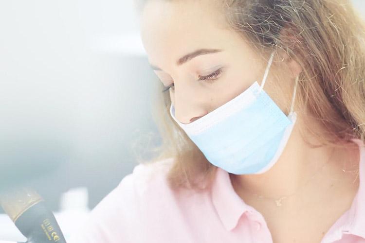 Mitarbeiterin reinigt die Zähne zur Vorsorge von Parodontitis in Wien